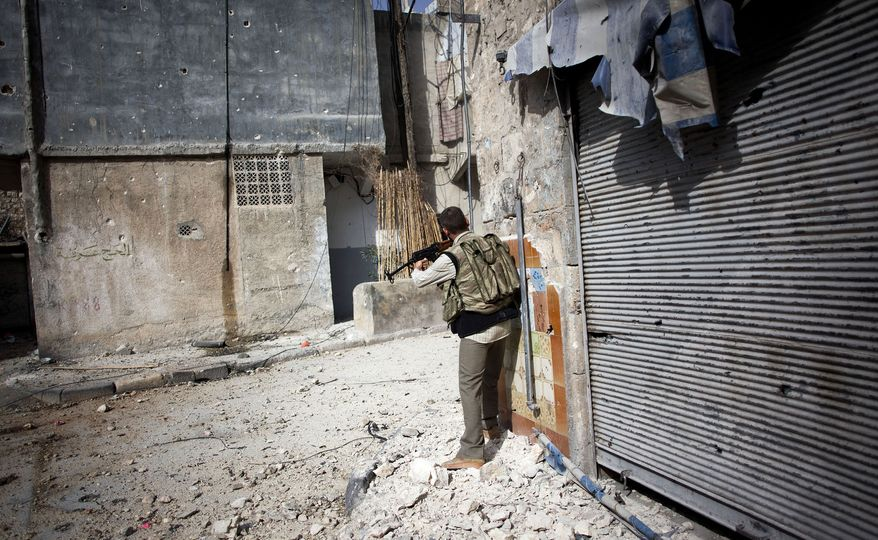 A Free Syrian Army fighter fires his weapon toward Syrian army positions in the Karmal Jabl district of Aleppo, Syria, on Sunday, Oct. 21, 2012. (AP Photo/Manu Brabo)
