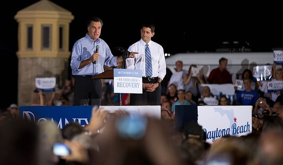 Republican presidential candidate, former Massachusetts Gov. Mitt Romney, left, speaks as vice presidential running mate Rep. Paul Ryan, R-Wis., watches on during a campaign rally on Friday, Oct. 19, 2012 in Daytona Beach, Fla.  (AP Photo/ Evan Vucci)
