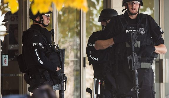 Police stand with guns drawn at the entrance to Brookfield Square Mall across from the scene of a shooting at Azana Salon in Brookfield, Wis. on Sunday , Oct. 21, 2012.  Police identified the shooting suspect as Radcliffe Franklin Haughton, 45, of Brown Deer, Wis.  Brookfield Police Chief Dan Tushaus said Haughton's car had been found, but he was still at large. Three people have been killed and four others have been wounded.   (AP Photo/Tom Lynn)