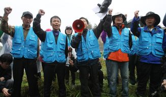 North Korean defectors shout slogans as police block their planned rally on a road in Paju, South Korea, near the Demilitarized Zone, on Monday, Oct. 22, 2012. The activists launched balloons with anti-Pyongyang propaganda leaflets to the North despite a ban by the South Korean government. (AP Photo/Ahn Young-joon)