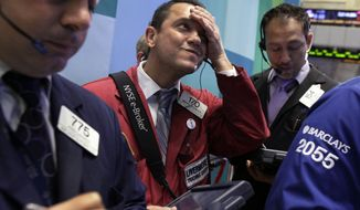 Trader Michael Zicchinolfi (center) works on the floor of the New York Stock Exchange on Monday, Oct. 22, 2012. (AP Photo/Richard Drew)