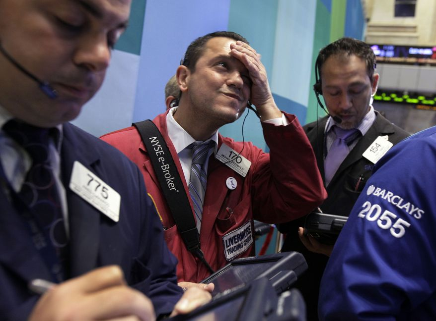Trader Michael Zicchinolfi (center) works on the floor of the New York Stock Exchange on Monday, Oct. 22, 2012. (AP Photo/Richard Drew)