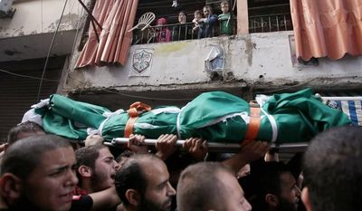 A Palestinian family Tuesday look at mourners carrying Ahmad Queider, 20, a Palestinian killed Monday during an exchange of gunfire in Beirut, where fighting was touched off by the assassination of an anti-Syrian intelligence chief. (Associated Press)