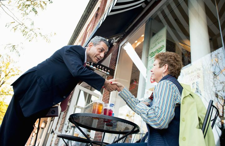 Independent Rob Sobhani, greeting Donna Walsh in Annapolis, and Republican Dan Bongino are confident of an upset in the race against Sen. Benjamin L. Cardin, though the Democrat has a healthy lead in polls. (Andrew Harnik/The Washington Times)