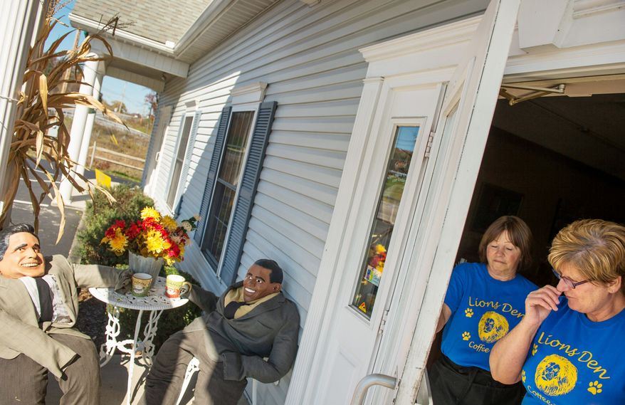 Linda Lee (right), the owner of the Lions Den Coffee Bar in Fisherville, Pa., has arranged straw men of President Obama and Gov. Mitt Romney, the Republican presidential nominee, having coffee together on the porch outside the front entrance on Monday as Nancy Jacobson looks on. (Andrew Harnik/The Washington Times)
