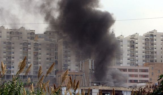 ** FILE ** Black smoke rises from a burning house in the northern port city of Tripoli, Lebanon, Oct. 22, 2012. (Associated Press)