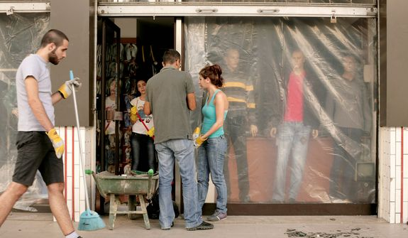 Workers gather to remove broken glass and debris at a clothing shop damaged in a car bomb attack that killed Brig. Gen. Wissam al-Hassan in the Achrafieh district of Beirut on Oct. 23, 2012. (Associated Press)