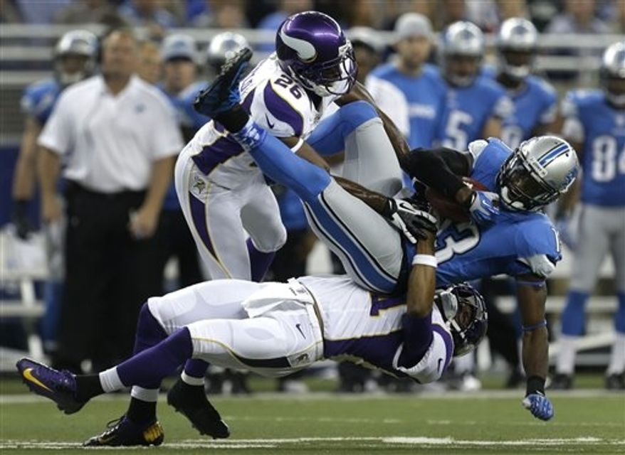 ** FILE ** Detroit Lions wide receiver Nate Burleson (13) is brought down by Minnesota Vikings cornerbacks Josh Robinson (21) and Antoine Winfield (26) in the 1st half of an NFL football game against the Detroit Lions in Detroit Sunday, Sept. 30, 2012. (AP Photo/Paul Sancya)