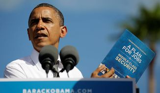 President Obama holds up a copy of his jobs and economic reform plan during a campaign event at the Delray Beach Tennis Center in Delray Beach, Fla., on Oct. 23, 2012, the day after the final presidential debate against Republican candidate Mitt Romney. (Associated Press)
