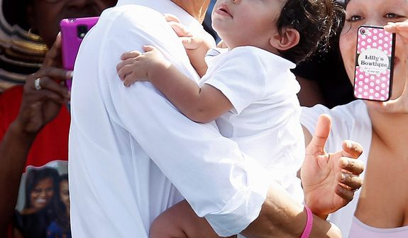 President Obama carries a baby as he prepares to leave a campaign stop in Delray Beach, Fla., on Tuesday, Oct. 23, 2012, a day after the last presidential debate with Republican candidate Mitt Romney. (AP Photo/Alan Diaz)