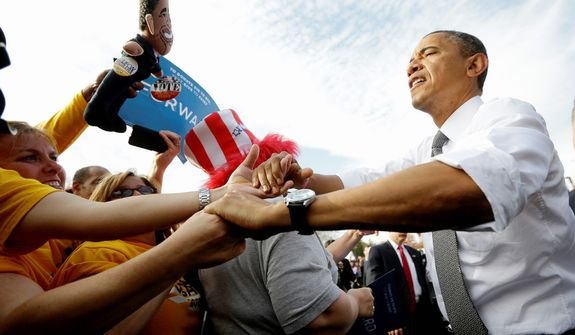 Supporters hold banners and a doll as President Barack Obama shakes hands with supporters during a campaign event at Triangle Park in Dayton, Ohio, Tuesday, Oct. 23, 2012, the day after the last presidential debate against Republican Presidential candidate, former Massachusetts Gov. Mitt Romney. (AP Photo/Pablo Martinez Monsivais)