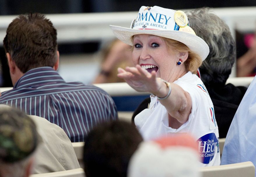 A supporter for Republican presidential candidate former Massachusetts Gov. Mitt Romney waves to friends while waiting for his arrival at a rally, Tuesday, Oct. 23, 2012, in Henderson, Nev. (AP Photo/Julie Jacobson)