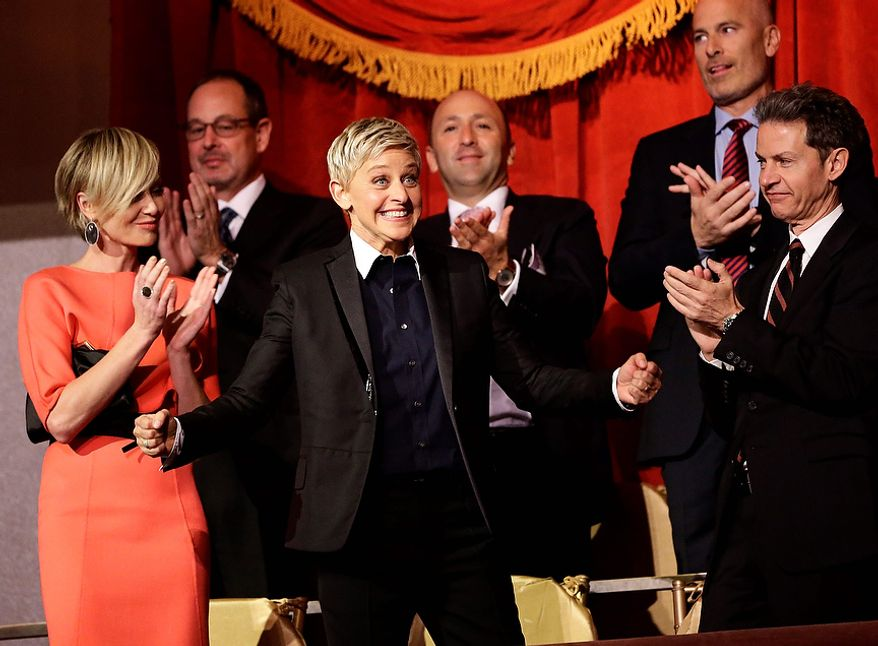 Entertainer Ellen DeGeneres, second from front left, reacts as she is introduced, with wife Portia de Rossi, left, before DeGeneres receives the 15th annual Mark Twain Prize for American Humor at the Kennedy Center, Monday, Oct. 22, 2012, in Washington. (AP Photo/Alex Brandon)