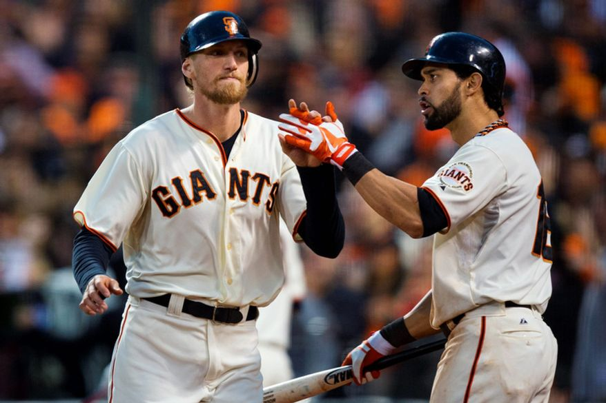 San Francisco Giants RF Hunter Pence (left) is congratulated by teammate Angel Pagan after scoring against the St. Louis Cardinals during the third inning of Game 7 of the National League Championship Series on Oct. 22, 2012, in San Francisco. (Associated Press/The Sacramento Bee)