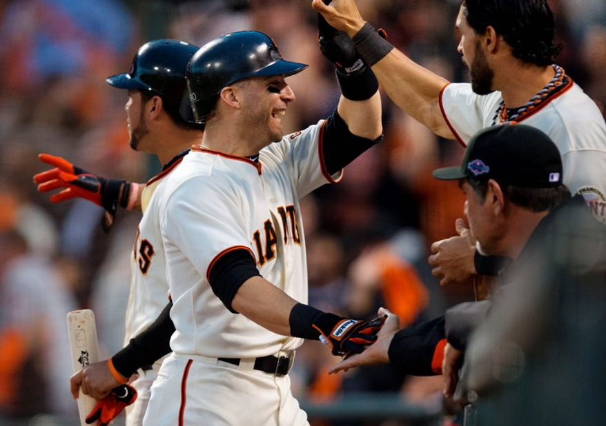 San Francisco Giants 2B Marco Scutaro (left) is congratulated by Angel Pagan after scoring a run against the St. Louis Cardinals during the third inning of Game 7 of the National League Championship Series on Oct. 22, 2012, in San Francisco. (Associated Press/The Sacramento Bee)