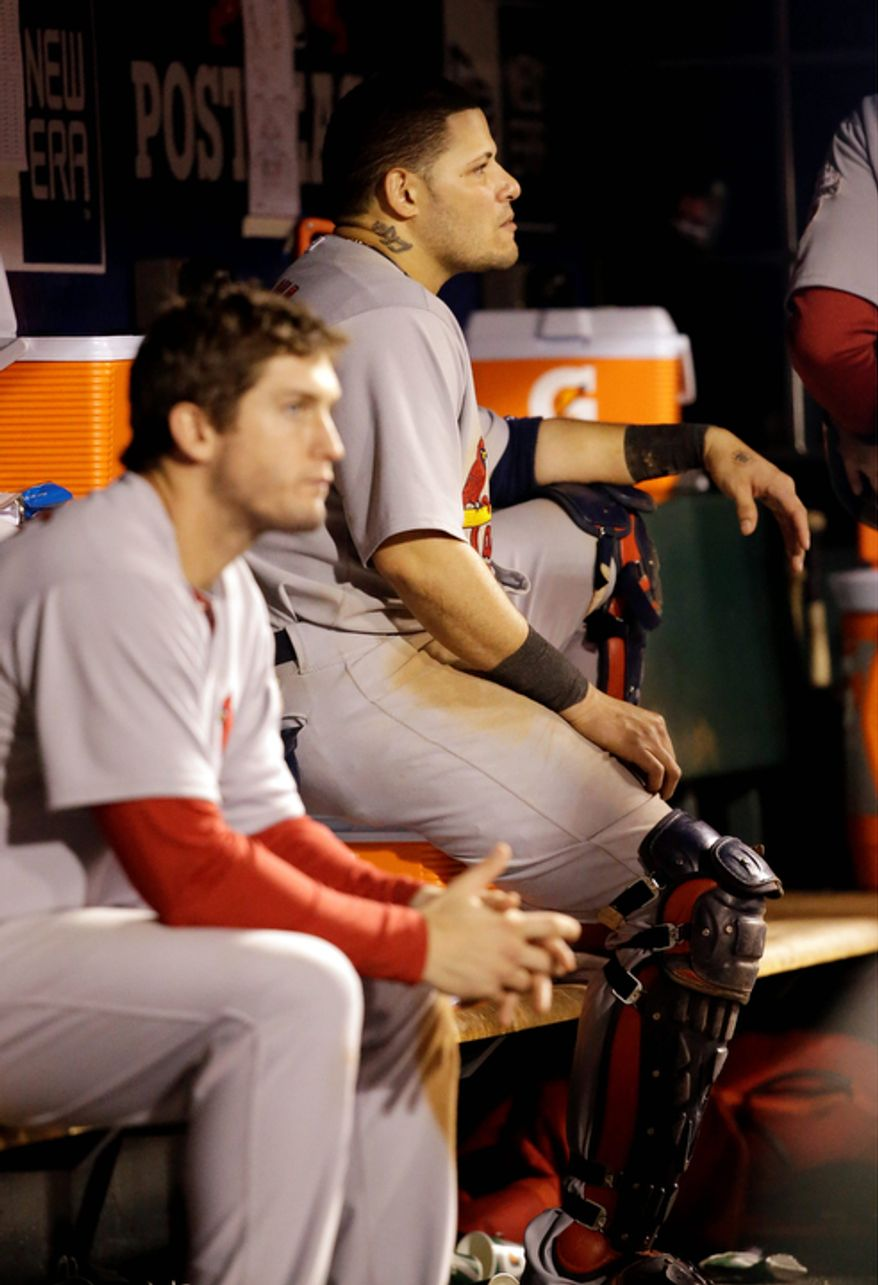 St. Louis Cardinals catcher Yadier Molina and 3B David Freese sit in the dugout during the seventh inning of Game 7 of the National League Championship Series between the Cardinals and the San Francisco Giants on Oct. 22, 2012, in San Francisco. (Associated Press)