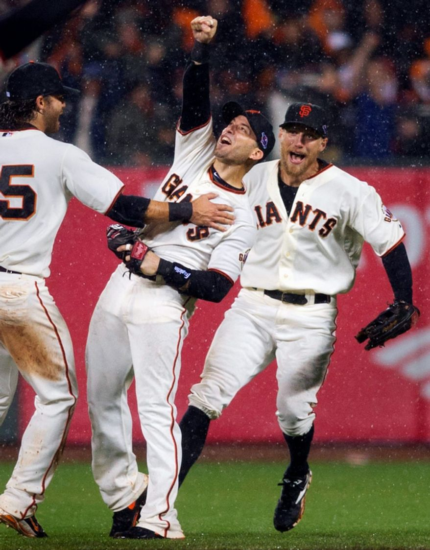 San Francisco Giants 2B Marco Scutaro (center) celebrates with teammates Hunter Pence (right) and Brandon Crawford after Scutaro made the final out of Game 7 of the National League Championship Series between the Giants and the St. Louis Cardinals on Oct. 22, 2012, in San Francisco. The Giants won, 9-0, to advance to the World Series. (Associated Press/The Sacramento Bee)