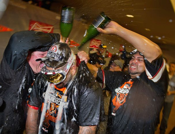 San Francisco Giants 3B Pablo Sandoval (center) is doused by pitcher Jose Mijares (right) in the clubhouse after Game 7 of the National League Championship Series between the Giants and the St. Louis Cardinals on Oct. 22, 2012, in San Francisco. The Giants won 9-0. (Associated Press/The Sacramento Bee)