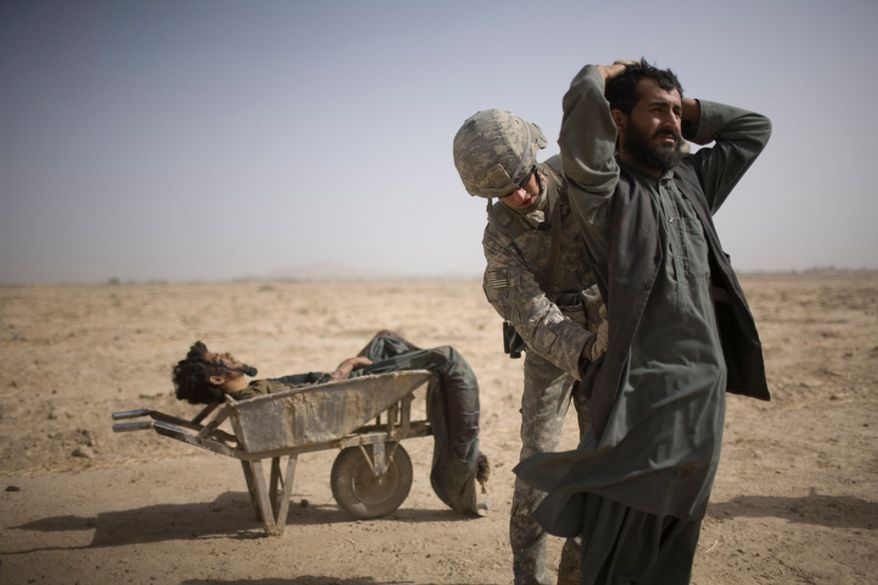 In this photo taken Sunday, Oct. 10, 2010, a US Army soldier from Scout Platoon 502 Infantry Regiment, 101st Airborne Division searches an associate of a suspected Taliban IED placer, seen in a wheelbarrow, who was killed in a coalition missile strike in Zhari district, Kandahar province. The Scouts' mission was to support roadside bomb clearance efforts in the militant stronghold, the latest days-long phase of Operation Dragon Strike. (AP Photo/Rodrigo Abd)