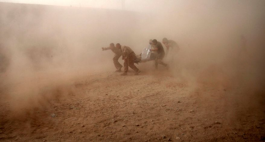 "U.S. Marines run through dust kicked up by a Black Hawk helicopter from Task Force Lift ""Dust Off"", Charlie Company 1-214 Aviation Regiment as they rush a colleague wounded in an IED strike for evacuation near Sangin, in the volatile Helmand Province of southern Afghanistan on Tuesday, May 10, 2011. (AP Photo/Kevin Frayer)"
