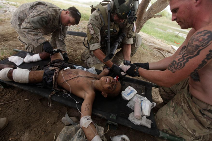 """During a helicopter rescue mission, Staff Sgt. Brenden Patterson, of Las Vegas, center, an Air Force Pararescueman, or """"PJ,"""" of the 58th Rescue Squadron, gets help from two U.S. soldiers, one of whom applies a tourniquet, left, as he treats an Afghan boy who stepped on an IED, severing his right foot and most of a hand, in Kandahar province, southern Afghanistan, Wednesday July 28, 2010. The PJs and helicopter aircrews are part of the U.S. Air Force's 451st Air Expeditionary Wing based at Kandahar Air Field, which provides a variety of air assets in southern Afghanistan. (AP Photo/Brennan Linsley)"""