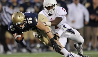Navy's Matt Aiken (85) runs the ball after making a reception as Indiana's Brian Williams makes the tackle during the second half of an NCAA college football game on Saturday, Oct. 20, 2012, in Annapolis, Md. Navy won 31-30.(AP Photo/Gail Burton).