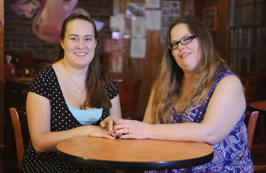 Jennie McCarthy (left) and Melisa Erwin sit in an ice cream parlor in Albany, N.Y., on Monday, Oct. 22, 2012. The couple has filed a discrimination complaint with the New York Division of Human Rights after, they say, they were turned away from a potential wedding site because they are gay. (AP Photo/Tim Roske)