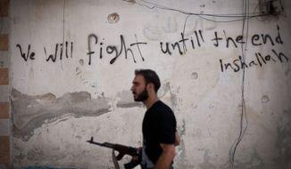 **FILE** A Free Syrian Army fighter walks Sept. 10, 2012, through a street in Amariya district in Aleppo, Syria. (Associated Press)
