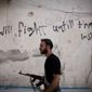 **FILE** A Free Syrian Army fighter walks Sept. 10, 2012, through a street in Amariya district in Aleppo, Syria. (Associated Press)