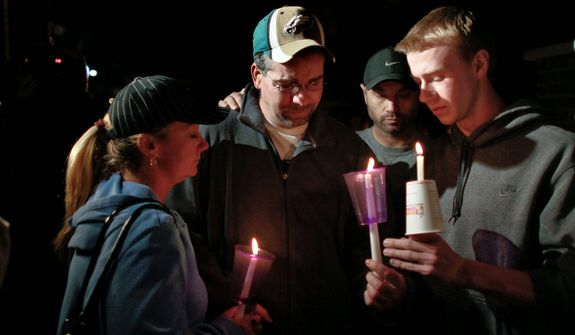 Anthony Pasquale (second from left), father of missing 12-year-old girl Autumn Pasquale, is comforted during a candlelight vigil on Oct. 22, 2012, in Clayton, N.J. (Associated Press)