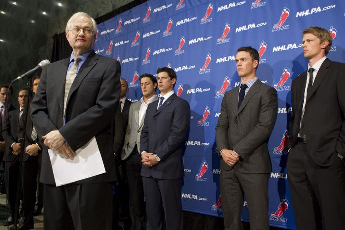 Donald Fehr, left, executive director of the NHL players' association, talks to reporters as he stands in front of players, including Sidney Crosby, center, following collective bargaining talks between the NHLPA and the NHL in Toronto on Thursday, Oct. 18, 2012. (AP Photo/The Canadian Press, Chris Young)