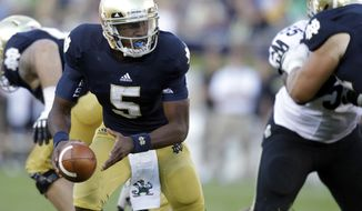 FILE - In this Sept. 8, 2012, file photo, Notre Dame quarterback Everett Golson (5) looks to hand off the ball during the second half of an NCAA college football game against Purdue in South Bend, Ind. Golson didn't do much last time out to make anyone think he'll be the quarterback who will lead Notre Dame back to glory, but coach Kelly remains firmly behind him, saying he sees him developing every day in practice. (AP Photo/Michael Conroy, File)