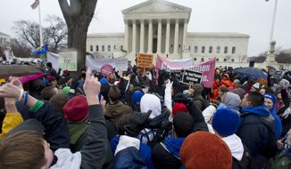 **FILE** Anti-abortion and abortion rights supporters stand face to face Jan. 23, 2012, in front of the Supreme Court in Washington during the annual March For Life rally. (Associated Press)
