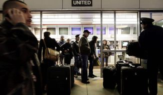 """Travelers check their luggage at O'Hare International Airport in Chicago two days before last Christmas. There are bargains on travel during """"dead zone"""" periods not so close to holidays, according to those in the know. (Associated Press)"""