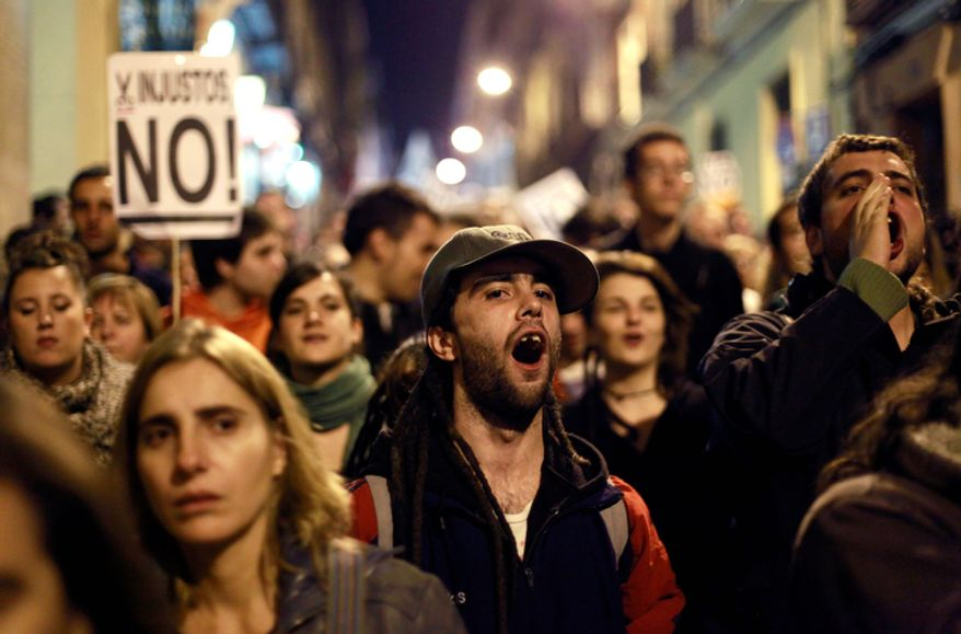 Protesters shout slogans during a demonstration outside Parliament as lawmakers debate budget spending cuts for 2013 in Madrid on Oct. 23, 2012. (Associated Press)