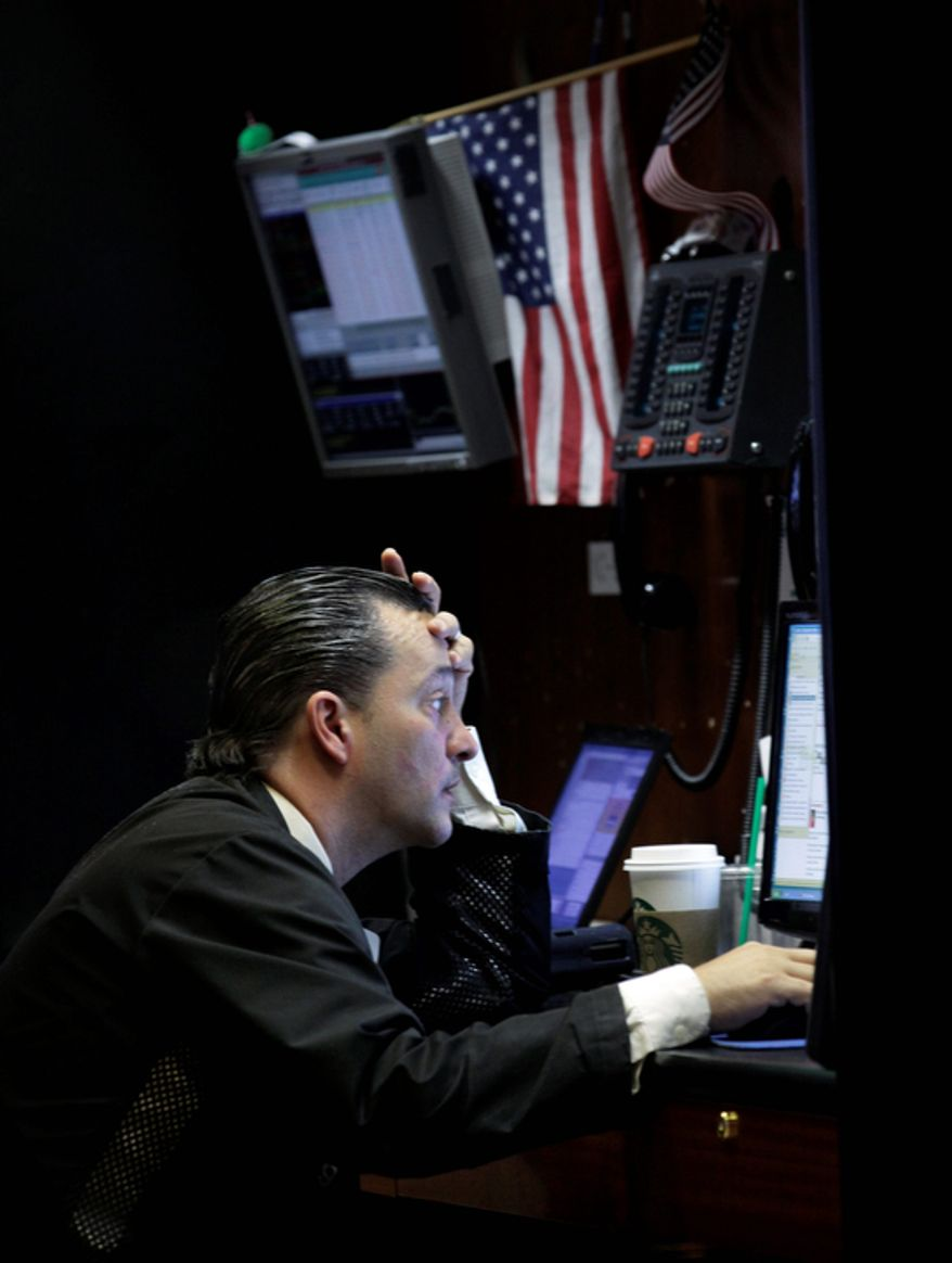 A trader sits Oct. 23, 2012, at his booth on the floor of the New York Stock Exchange. (Associated Press)