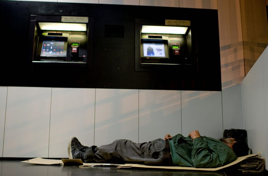 A homeless man sleeps Oct. 23, 2012, on a piece of cardboard next to cash dispenser in Pamplona, Spain. (Associated Press)