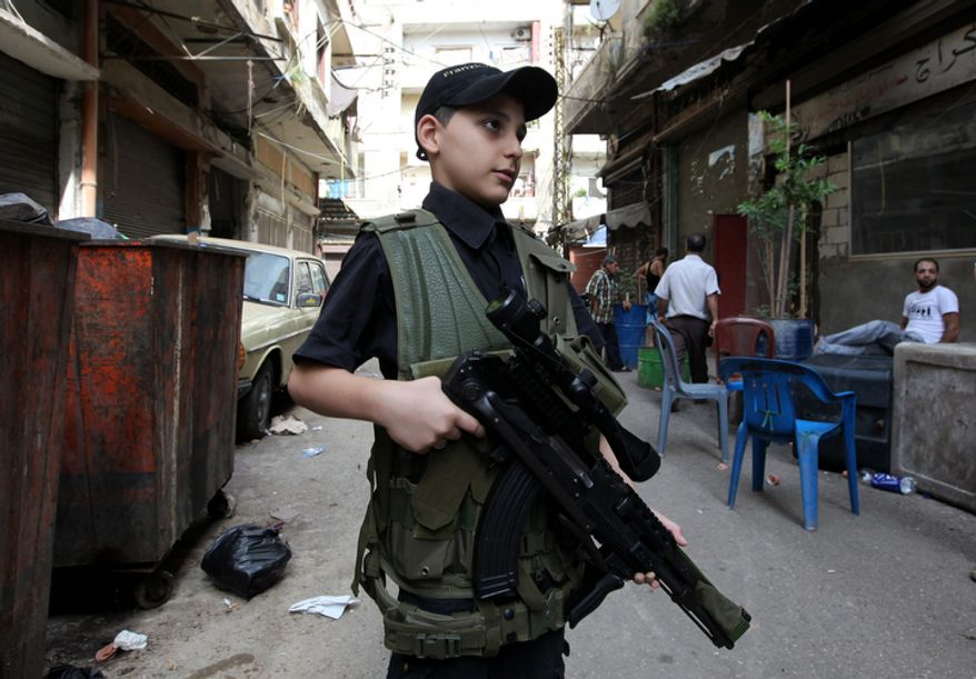 Usam, 10, an armed Sunni boy, poses for a photo Oct. 22, 2012, during clashes that erupted in the northern port city of Tripoli, Lebanon. Lebanese troops launched a major security operation to open all roads and force gunmen off the streets, trying to contain an outburst of violence set off by the assassination of a top intelligence official who was a powerful opponent of Syria. (Associated Press)