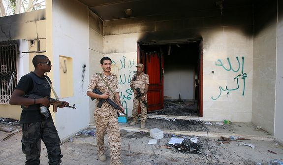 ** FILE ** Libyan military guards check one of the burned-out buildings at the U.S. Consulate in Benghazi, Libya, on Saturday, Sept. 14, 2012, during a visit by Libyan President Mohammed el-Megarif to express sympathy for the death of J. Christopher Stevens, the U.S. ambassador to Libya, and his colleagues in the Sept. 11 attack on the consulate. (Associated Press)