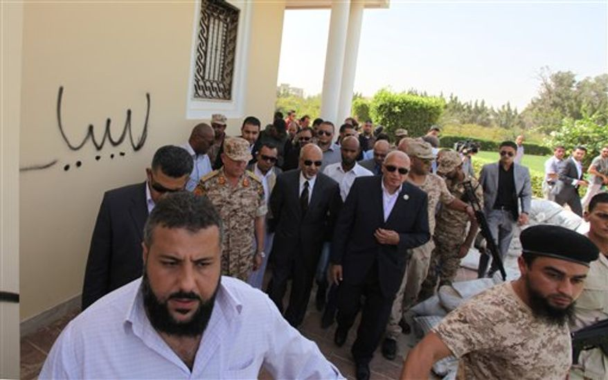 **FILE** President Mohammed el-Megarif (center) visits the U.S. Consulate in Benghazi, Libya, on Sept. 14, 2012, to express sympathy for the death of U.S. Ambassador Chris Stevens and his colleagues in the Sept. 11 attack on the consulate. (Associated Press)