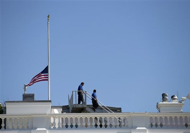 **FILE** White House workers walk on the roof of the White House on Sept. 12, 2012, after lowering the flag to half-staff for the death of U.S. ambassador to Libya Christopher Stevens. (Associated Press)