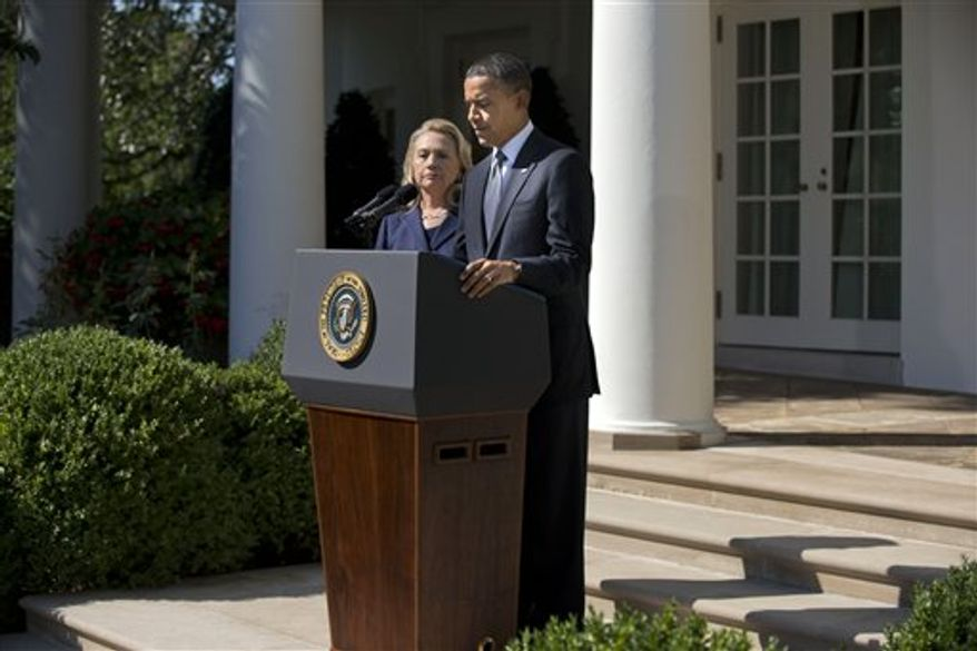 **FILE** Secretary of State Hillary Clinton looks on as President Obama delivers a statement Sept. 12, 2012, in the Rose Garden of the White House on the death of Christopher Stevens, U.S. ambassador to Libya. (Associated Press)