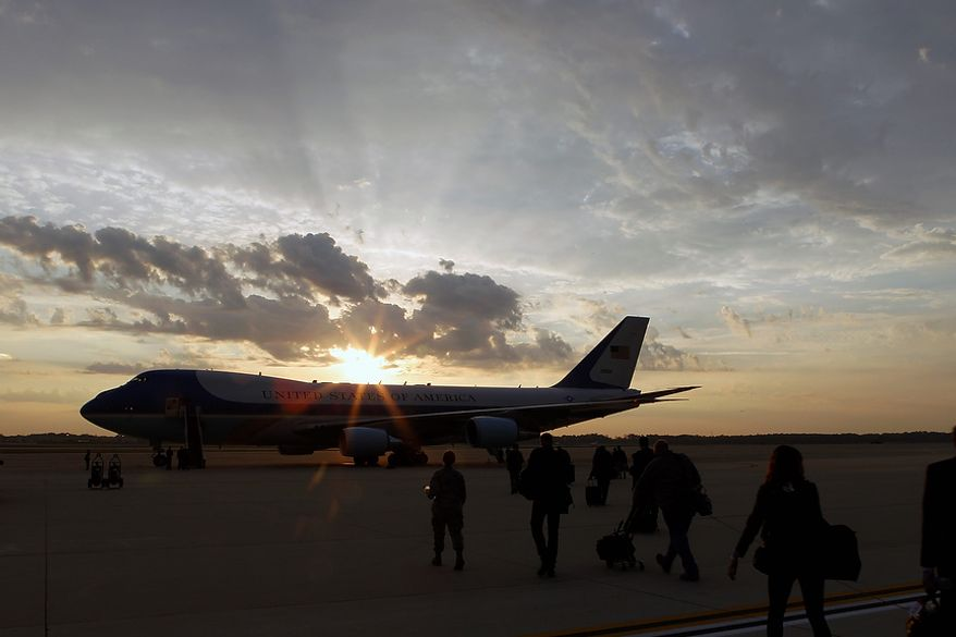 Members of the press pool board the silhouetted Air Force One before President Obama on Oct. 24, 2012, at Andrews Air Force Base, Md. The president began a two-day campaign blitz through eight states with stops in key battleground states Iowa, Colorado, Nevada, Ohio and Virginia. (Associated Press)