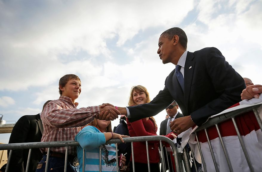 President Obama greets supporters Oct. 24, 2012, on the tarmac at the Quad Cities International Airport in Moline, Ill., upon his arrival aboard Air Force One. The president began a two-day campaign blitz through eight states with stops in key battleground states Iowa, Colorado, Nevada, Ohio and Virginia. (Associated Press)