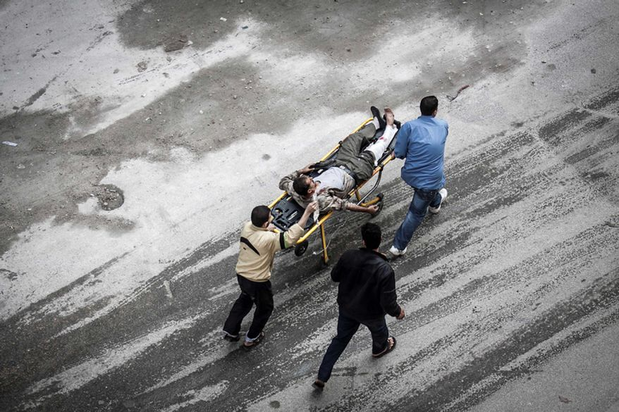 Syrians wheel a man injured from an artillery shell that landed near a bakery to a hospital for treatment in Aleppo, Syria, on Tuesday, Oct. 23, 2012. Several were killed and a dozen were injured in the attack. (AP Photo/Narciso Contreras)