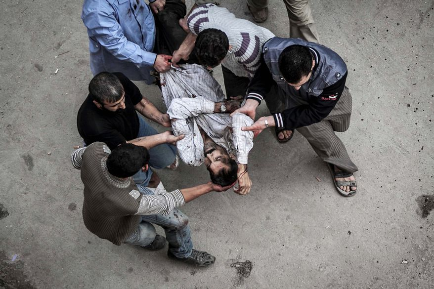 A man severely injured by an artillery shell that landed near a bakery is carried to a hospital for treatment in Aleppo, Syria, on Tuesday, Oct. 23, 2012. (AP Photo/Narciso Contreras)