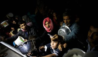 Displaced Syrian men wait for food near an NGO charitable kitchen in a refugee camp near Azaz, Syria, on Tuesday, Oct. 23, 2012. (AP Photo/Manu Brabo)