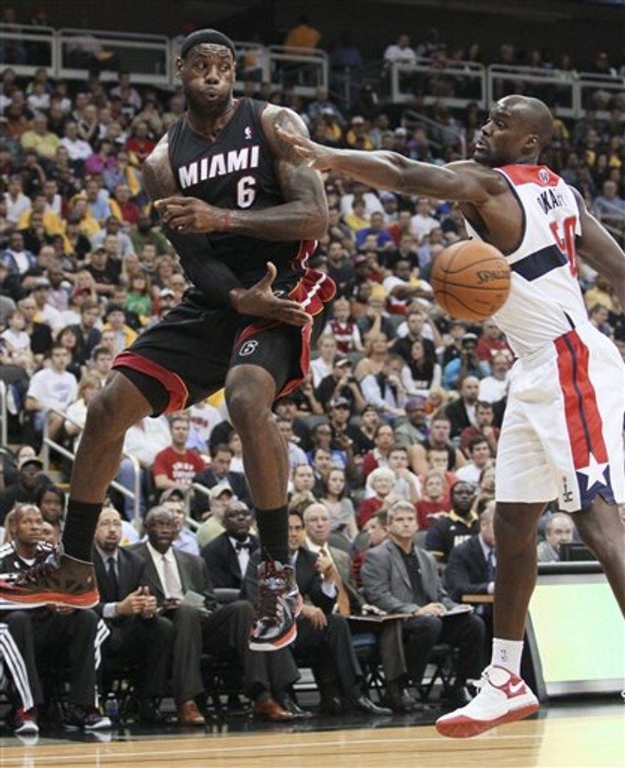 Miami Heat forward LeBron James (6) passes the ball as Washington Wizards center Emeka Okafor (50) defends during the first half of an NBA preseason game, Wednesday, Oct. 24, 2012, in Kansas City, Mo. (AP Photo/Colin E. Braley)