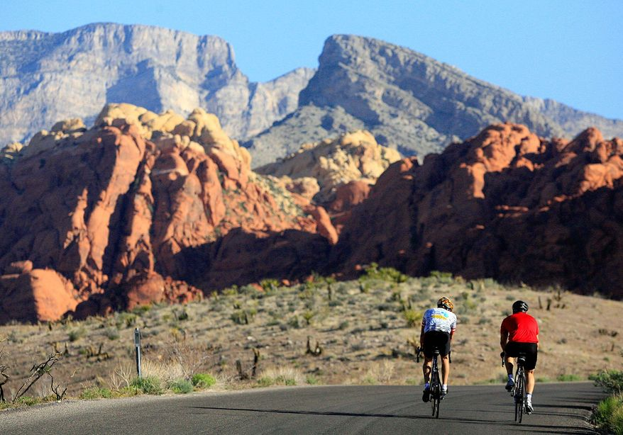 Two cyclists travel the 13-mile-long scenic drive at Red Rock Canyon National Conservation Area in Nevada. (Associated Press)