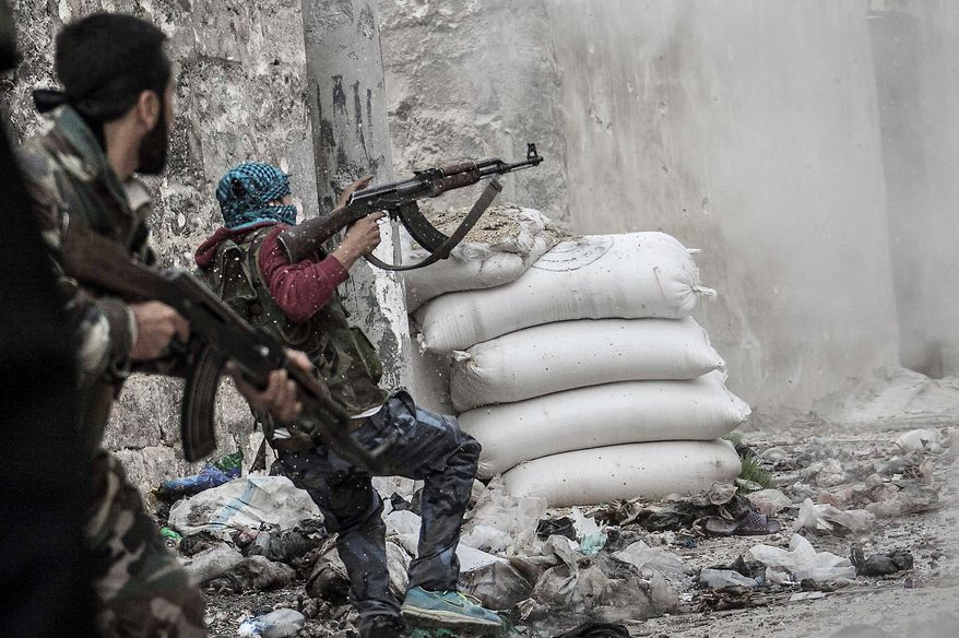A Syrian rebel retreats for cover from enemy fire at the Moaskar front line in the Karmal Jabl neighborhood of Aleppo. Heavy fighting was reported Thursday in the western cities of Allepo and Al Rastan. (Associated Press)